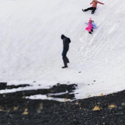 Kiddos having a blast on a snowbank