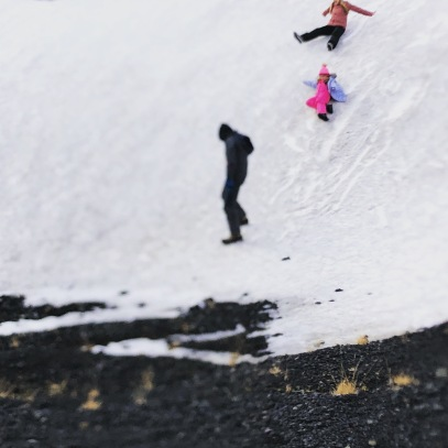 Kiddos having a blast on a snowbank