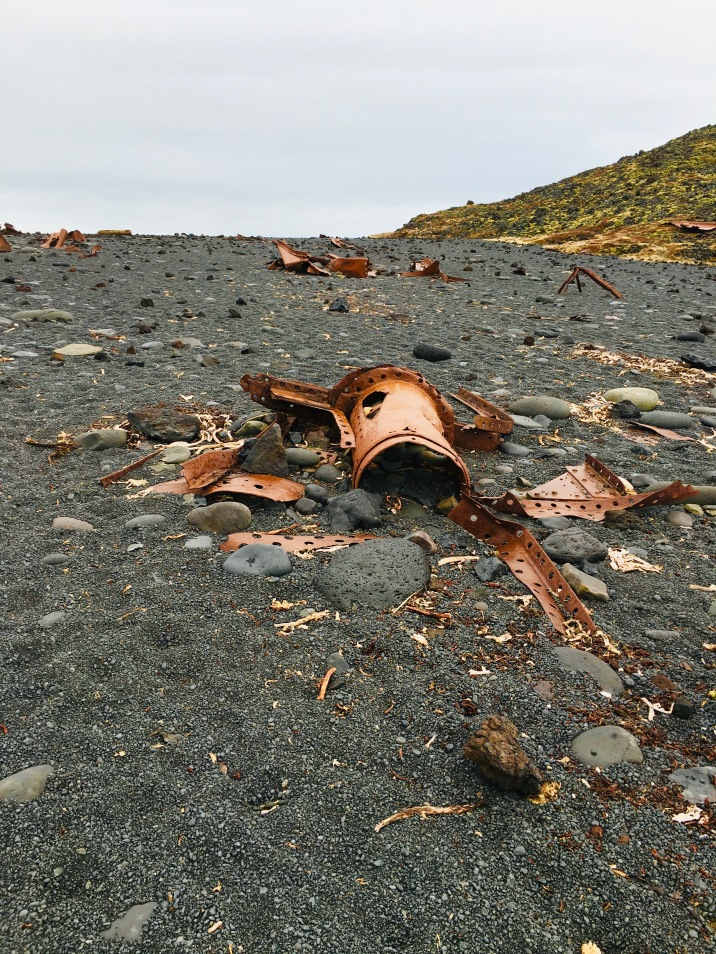 Debris from a wrecked ship provides contrast to the black pebble beach.